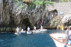 Rowers hover by the tiny cave to the Blue Grotto